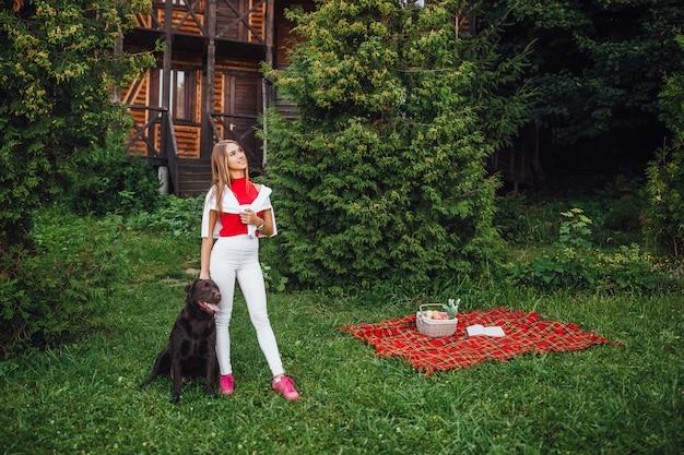 Junges schönes mädchen mit ihrem schwarzen hund labrador im park und freut sich