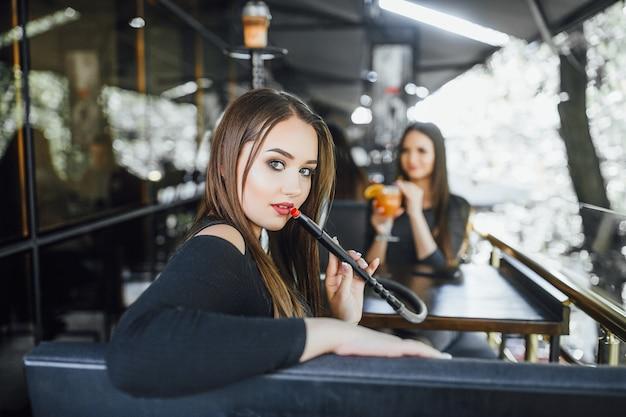 Junges schönes mädchen mit ihrer freundin, sitzt und raucht eine wasserpfeife auf der sommerterrasse eines modernen cafés.