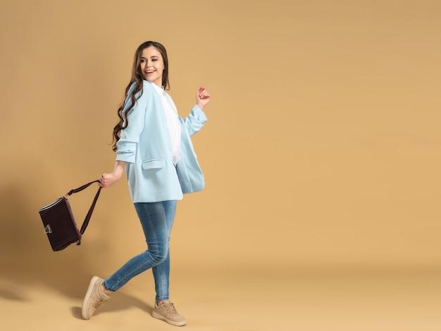 Junges schönes mädchen mit langen fließenden haaren in einem weißen hemd und einer blauen jacke geht auf einem pastellorange mit einer tasche in ihrer hand.