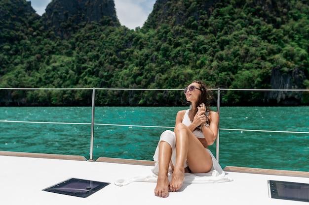 Junges schönes mädchen mit langen haaren, die auf dem bug der yacht im weißen rock und im bikini sitzen.