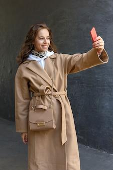 Junges schönes mädchen mit langen haaren im beige mantel, der selfie nimmt