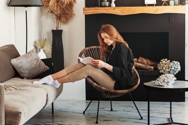 Junges schönes mädchen mit langen haaren liest ein buch, das auf einem stuhl im wohnzimmer sitzt