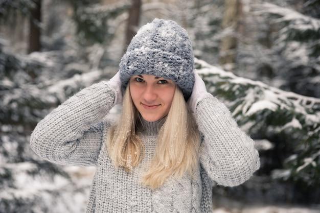 Junges schönes mädchen mit langen weißen haaren spielt schneebälle. sie hat spaß, wirft schnee und freut sich über den schneefall. winterspaziergang draußen.