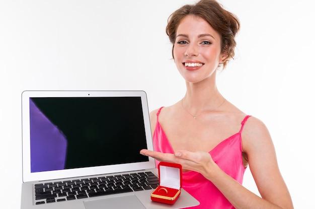 Junges schönes mädchen mit welligem braunem geflicktem haar, sauberer haut, flachen zähnen, schönem lächeln, im rosa trikot, hält eine trainingsringbox und laptop