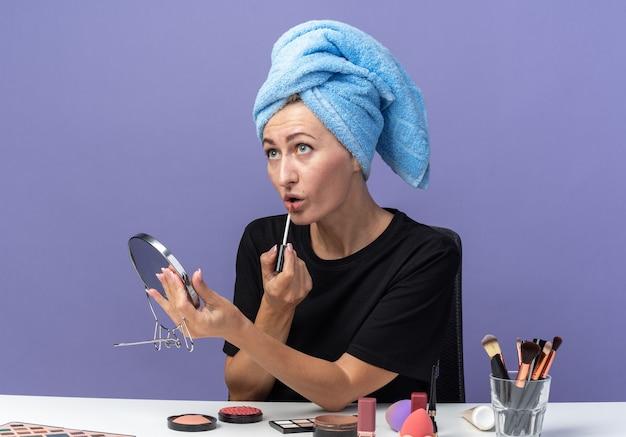 Junges schönes mädchen nachschlagen sitzt am tisch mit make-up-tools, die haare im handtuch abwischen, spiegel halten und lipgloss auf blauer wand auftragen