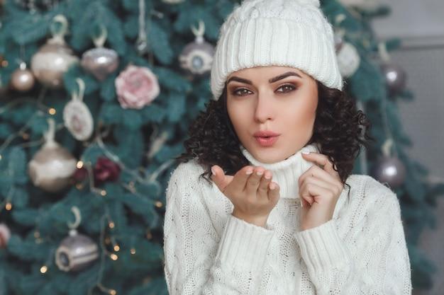Junges schönes mädchen nahe dem weihnachtsbaum und lächelnd. fröhliche hübsche frau, die einen luftkuss sendet