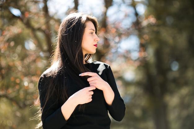 Junges schönes mädchen posiert in einer schwarzen lederjacke im park