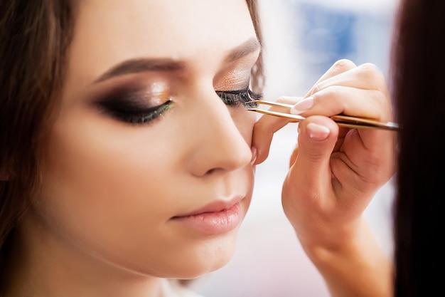 Junges, schönes mädchen setzte ein make-up in einen schönheitssalon ein