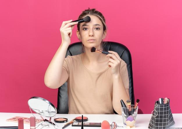 Junges schönes mädchen sitzt am tisch mit make-up-tools, die puderrouge einzeln auf rosa hintergrund auftragen
