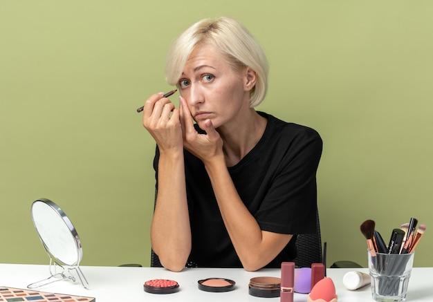 Junges schönes mädchen sitzt am tisch mit make-up-tools zeichnen pfeil mit eyeliner isoliert auf olivgrünem hintergrund