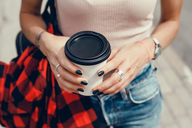 Junges schönes mädchen trinkt kaffee in einem glas auf der straße, lacht und lächelt