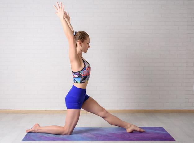 Junges schönes mädchen übt yoga zu hause.