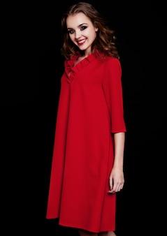 Junges schönes mode-modell, das rotes kleid mit gelockter frisur auf schwarzem trägt
