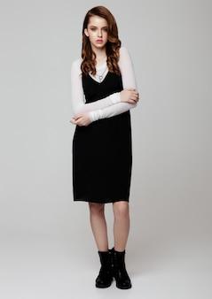 Junges schönes mode-modell, das schwarzes kleid mit weißem hemd auf grau trägt