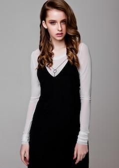 Junges schönes mode-modell, das schwarzes kleid mit weißem hemd auf weiß trägt