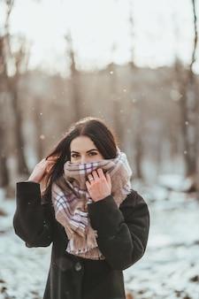 Junges schönes modell, das im winterwald aufwirft. stilvolles modeporträt