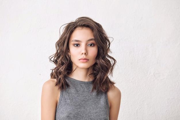 Junges schönes modell mit natürlichem make-up und schönem haar auf weißem hintergrund in einem grauen t-shirt