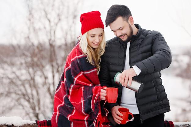 Junges schönes paar bei einem picknick im winter trinken sie kaffee