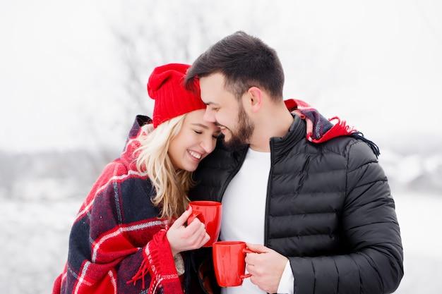 Junges schönes paar bei einem picknick im winter trinken sie kaffee Premium Fotos