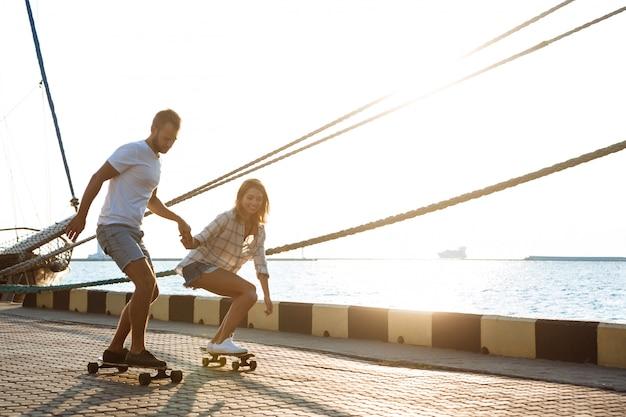 Junges schönes paar, das am meer, skateboarding geht.