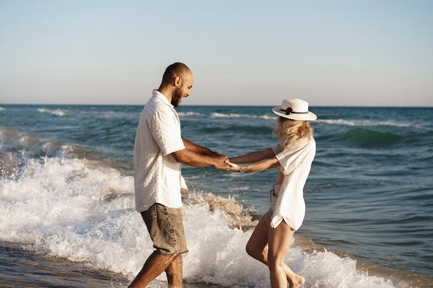 Junges schönes paar, das am strand nahe meer geht