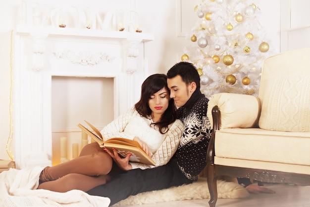 Junges schönes paar, das auf weihnachtszeit liest