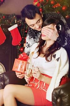 Junges schönes paar, das geschenke an weihnachten austauscht