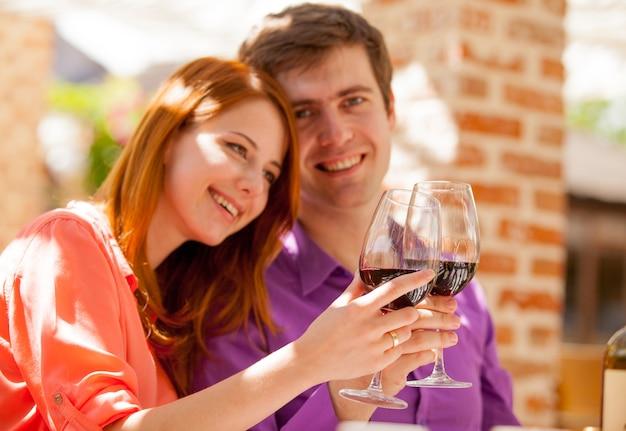 Junges schönes paar, das glas wein im restaurant trinkt.