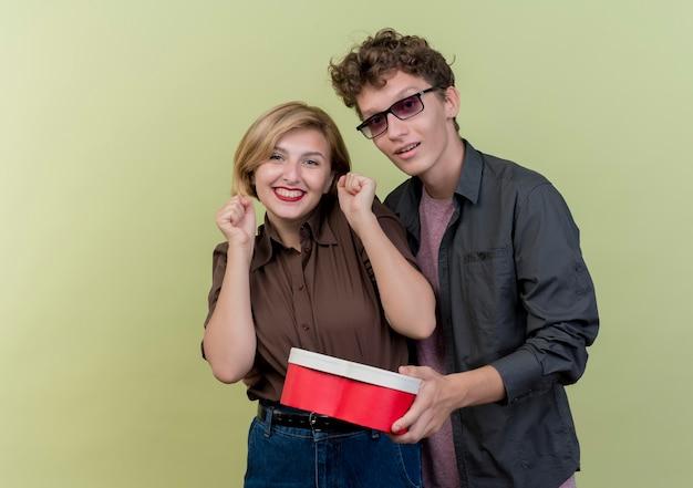 Junges schönes paar, das glücklichen mann der freizeitkleidung hält, der geschenkbox für ihre lächelnde fröhliche freundin über licht hält