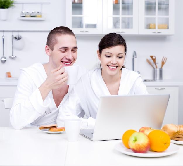 Junges schönes paar, das in der küche sitzt und laptop betrachtet