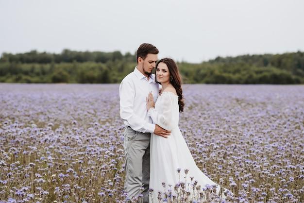 Junges schönes paar, das in einem blühenden lila feld steht