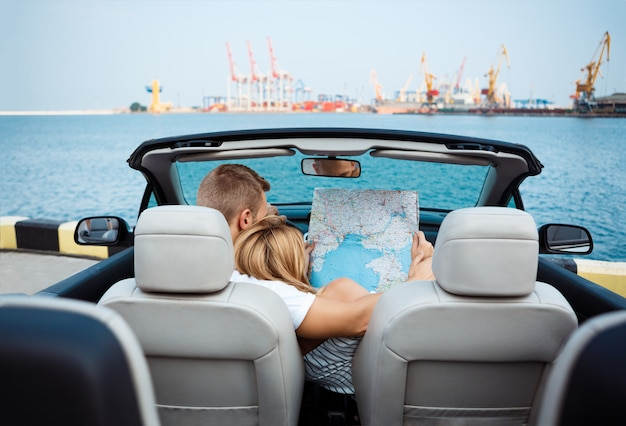 Junges schönes paar, das karte betrachtet, im auto sitzend.