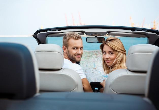 Junges schönes paar, das karte hält, im auto nahe der seeküste sitzend