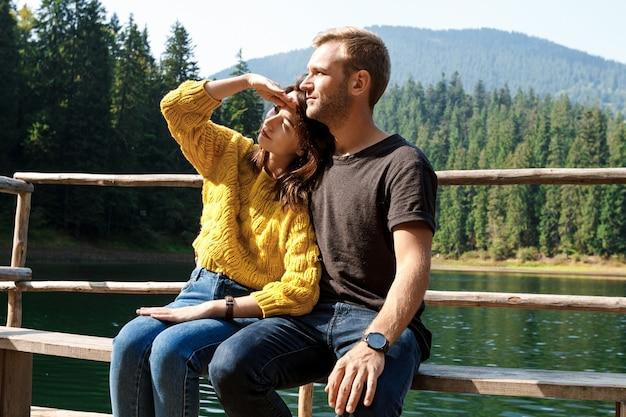 Junges schönes paar, das lächelt, umarmt und berge lanscape genießt