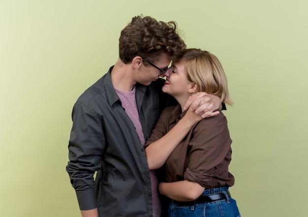 Junges schönes paar, das lässige kleidung jungen und mädchen glücklich in der liebe umarmt über lichtwand trägt