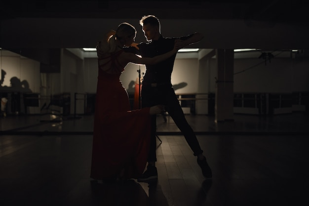 Junges schönes paar, das mit leidenschaft tanzt