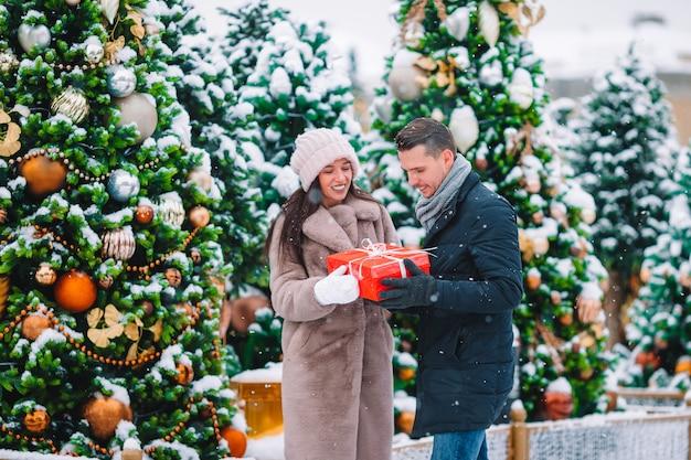 Junges schönes paar, das weihnachten in der stadtstraße feiert und einander geschenk gibt