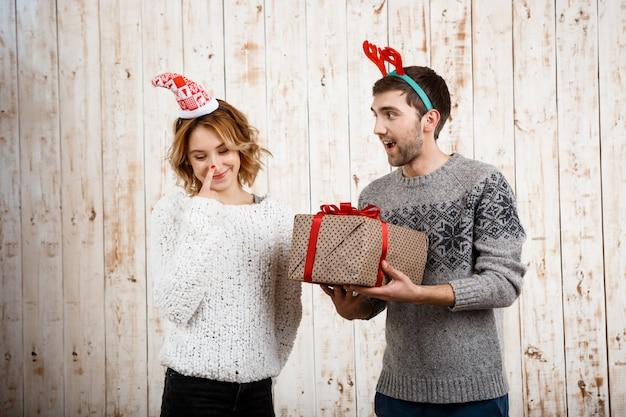 Junges schönes paar, das weihnachtsgeschenk über holzwand hält