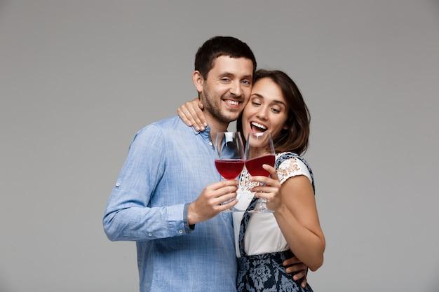 Junges schönes paar, das wein trinkt und über graue wand lächelt