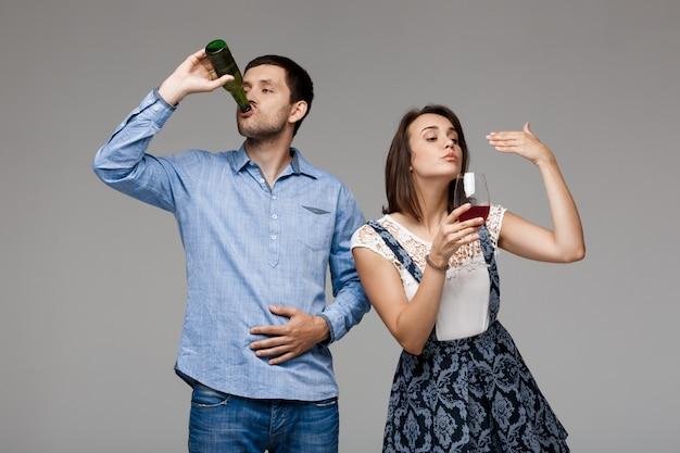 Junges schönes paar, das wein und bier über graue wand trinkt