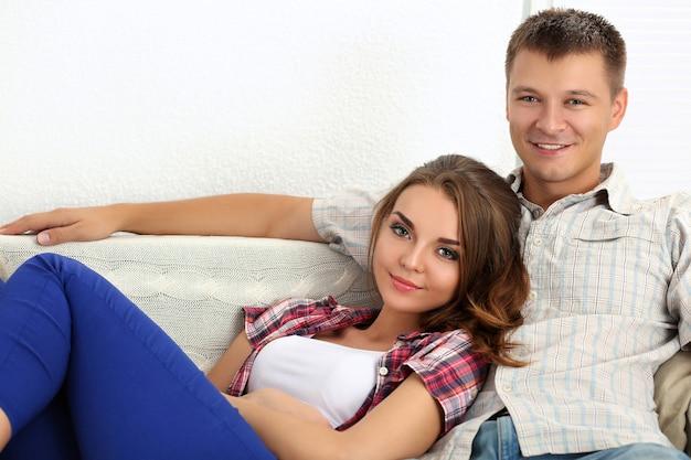 Junges schönes paar, das zusammen auf sofa in neuen wohnungen sitzt