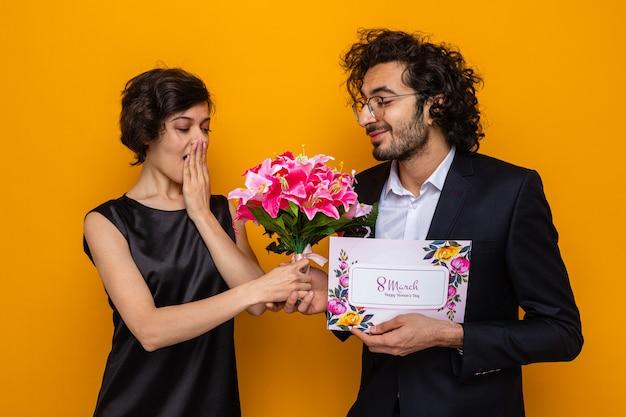 Junges schönes paar glücklicher mann mit grußkarte, die seiner überraschten und glücklichen freundin einen blumenstrauß gibt, der den internationalen frauentag am 8. märz feiert