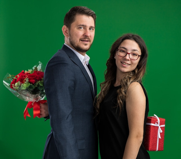 Junges schönes paar glücklicher mann und frau, die geschenke voreinander verstecken, glücklich in der liebe zusammen feiern den valentinstag, der über grüner wand steht