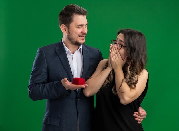 Junges schönes paar, gutaussehender mann, der eine rote schachtel mit verlobungsring hält, um seiner reizenden aufgeregten freundin einen vorschlag zu machen, der den valentinstag über grüner wand feiert