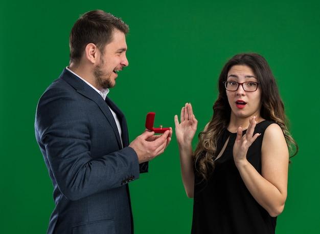 Junges schönes paar, gutaussehender mann, der eine rote schachtel mit verlobungsring hält und seiner reizenden aufgeregten freundin, die über grüner wand steht, einen vorschlag machen wird