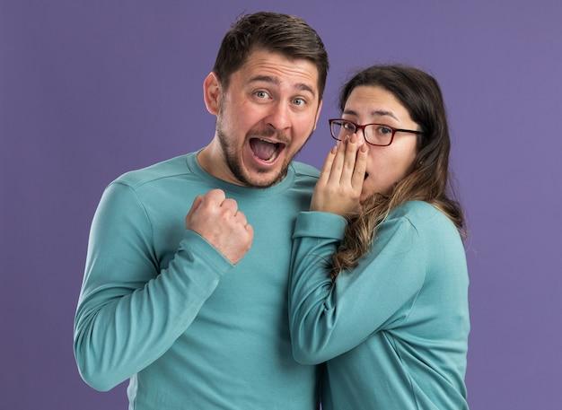 Junges schönes paar in blauer freizeitkleidung frau, die ihrem aufgeregten freund ein geheimnis erzählt