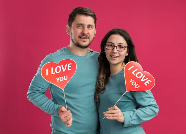 Junges schönes paar in blauer freizeitkleidung, mann und frau, die herzen auf stöcken halten, lächeln fröhlich glücklich in der liebe zusammen und feiern valentinstag über rosa wand