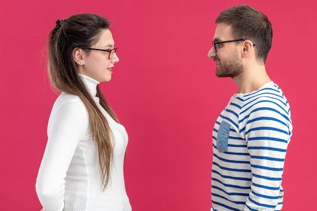 Junges schönes paar in der glücklichen kleidung des glücklichen mannes und der frau, die einander lächelnd betrachten und valentinstag feiern, der über rosa hintergrund steht