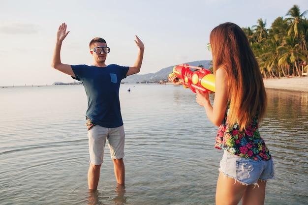 Junges schönes paar in der liebe, die am tropischen strand spielt, sommerferien, honigmond, romantik, sonnenuntergang, glücklich, spaß haben, wasserpistole, kampf, mann gibt auf, positiv, lustig