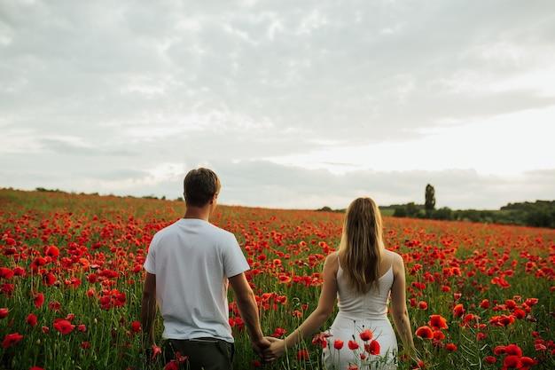 Junges schönes paar in der liebe, die hände auf einer grünen wiese voller mohnblumen hält